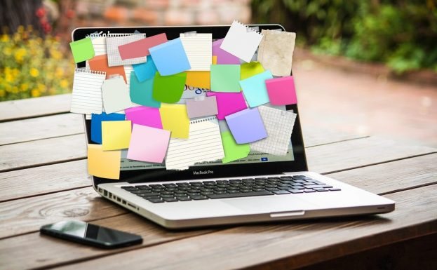 Computer covered in post it notes